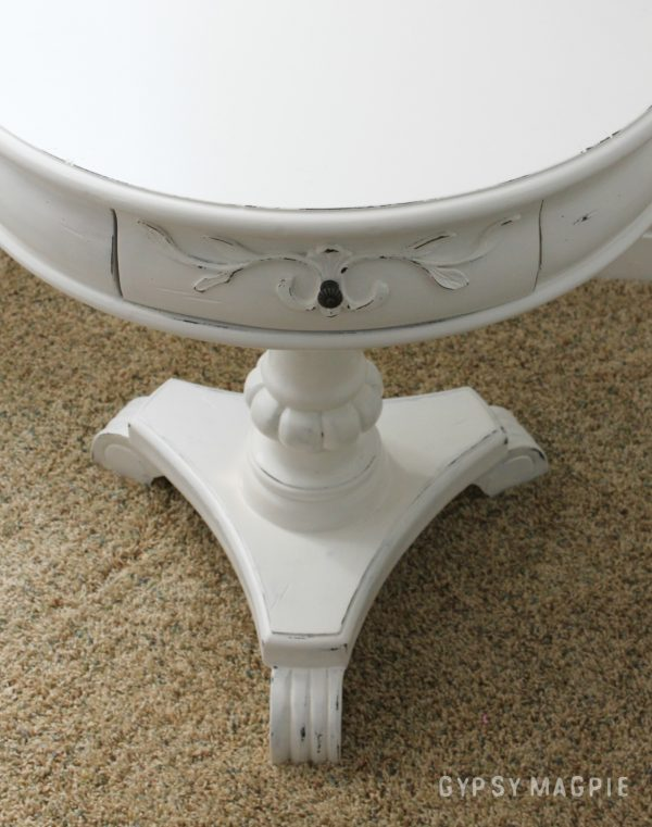 White pedestal table with papered drawers. Darling!